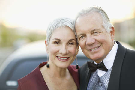 Portrait of well dressed senior couple smiling outdoors
