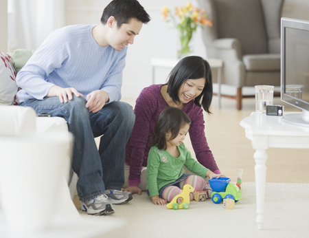 Mother and father playing with daughter in livingroom LANG_EVOIMAGES
