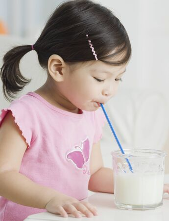 Mixed race girl drinking milk with straw