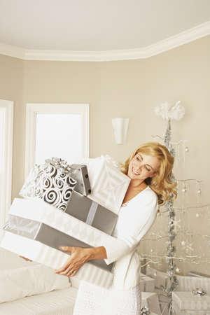 Hispanic woman holding stack of Christmas gifts