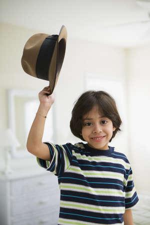 Hispanic boy holding old-fashioned hat