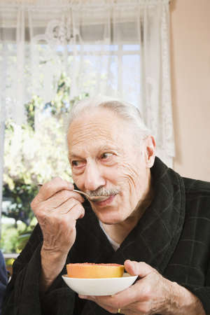 Senior man eating grapefruit