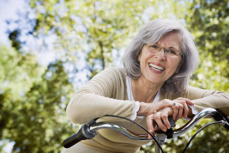 Senior Hispanic woman leaning on bicycle outdoors LANG_EVOIMAGES