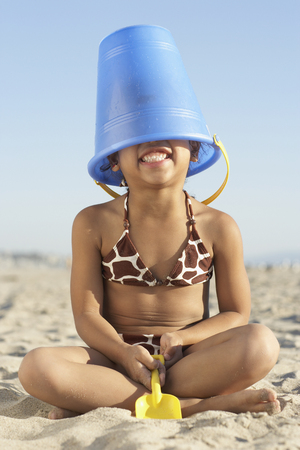 Young mixed race girl with bucket on head at beach