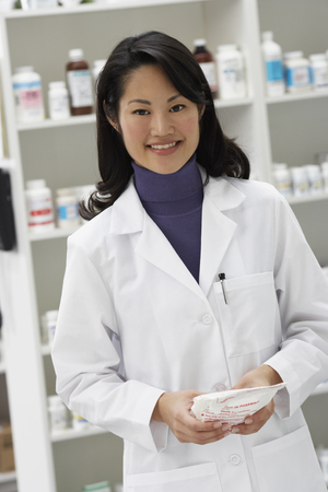 Portrait of Asian female pharmacist in pharmacy LANG_EVOIMAGES