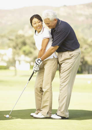 Senior Asian man helping wife with golf swing LANG_EVOIMAGES