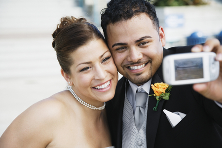 Multi-ethnic bride and groom taking own photograph LANG_EVOIMAGES