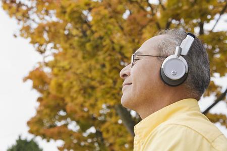 Hispanic man wearing headphones outdoors