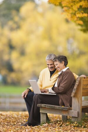 African couple using laptop on park bench in autumn
