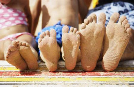Close up of familys sandy feet at beach