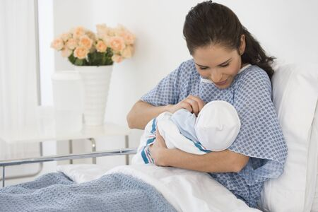 Hispanic mother holding newborn baby in hospital bed LANG_EVOIMAGES
