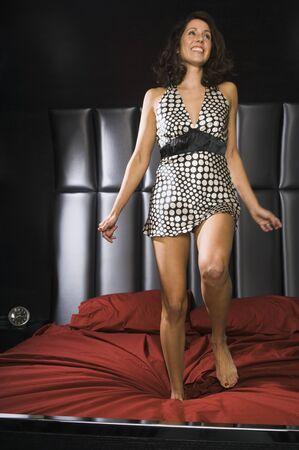 Hispanic woman jumping on bed