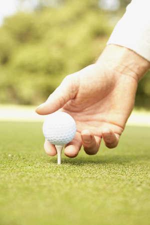 Close up of man putting golf ball on tee