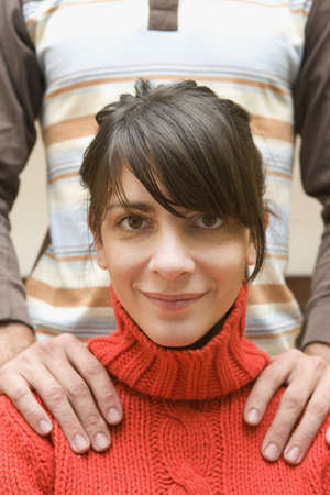 Close up of woman smiling with mans hands on her shoulders LANG_EVOIMAGES