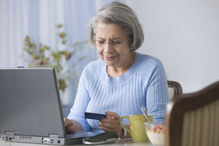 Senior Hispanic woman shopping online with credit card LANG_EVOIMAGES