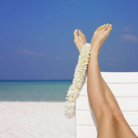 Womans feet with lei at beach