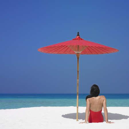 Woman sitting under umbrella at beach
