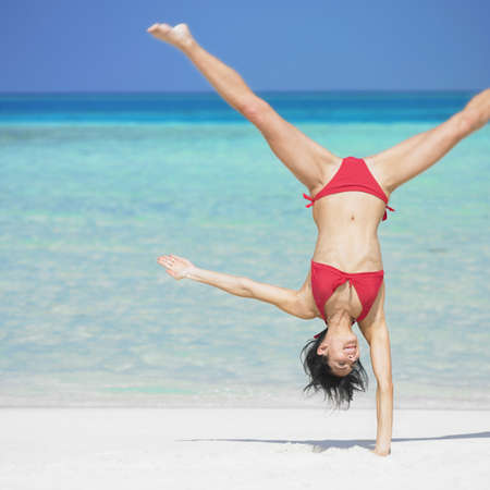 Woman doing hand stand at beach LANG_EVOIMAGES