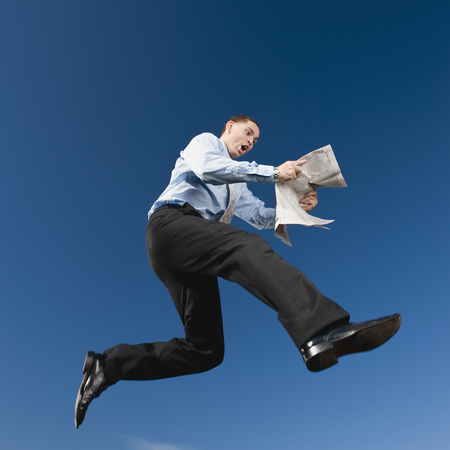 African businessman reading newspaper in mid-air LANG_EVOIMAGES