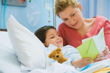 Madre que lee la tarjeta a la hija en la cama de hospital LANG_EVOIMAGES