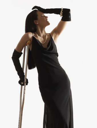 Pacific Islander woman in evening gown leaning on crutch