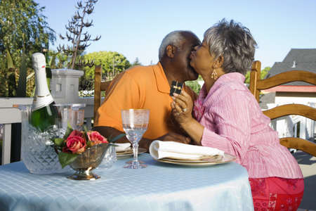Senior African couple kissing at table with champagne