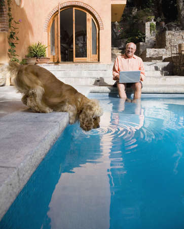 Senior man laughing at dog drinking from swimming pool