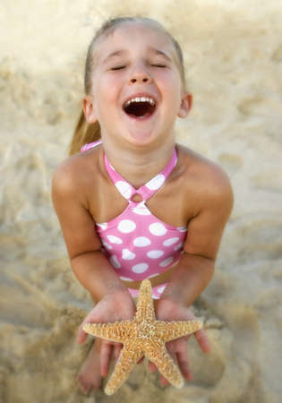 High angle view of girl holding starfish at beach