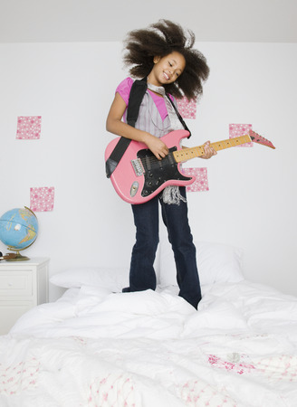 African girl playing guitar on bed