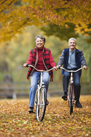 African couple riding bicycles in park in autumn