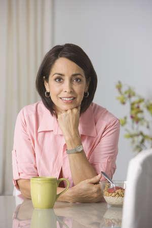 Hispanic woman eating breakfast