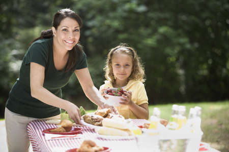 Hispanic mother and daughter having picnic outdoors LANG_EVOIMAGES