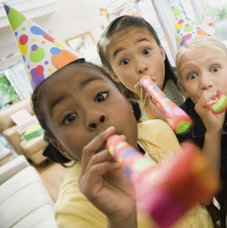 Children blowing noisemakers at birthday party