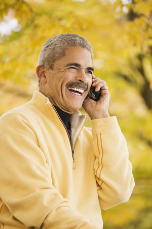 African man using cell phone outdoors in autumn