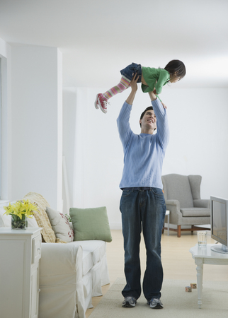 Father holding daughter above head