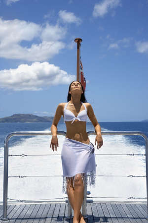 Pacific Islander woman on stern of boat LANG_EVOIMAGES