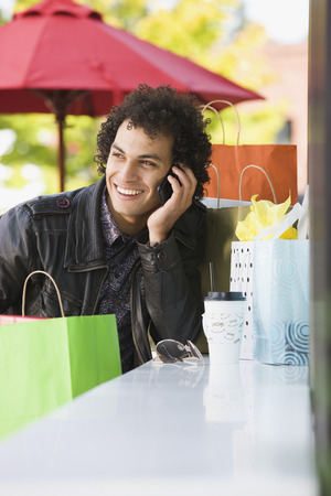 Middle Eastern man with shopping bags talking on cell phone LANG_EVOIMAGES