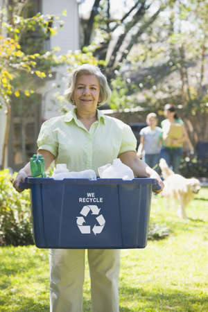 Hispanic woman carrying recycling bin