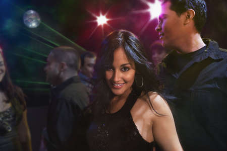 Hispanic friends dancing in nightclub LANG_EVOIMAGES