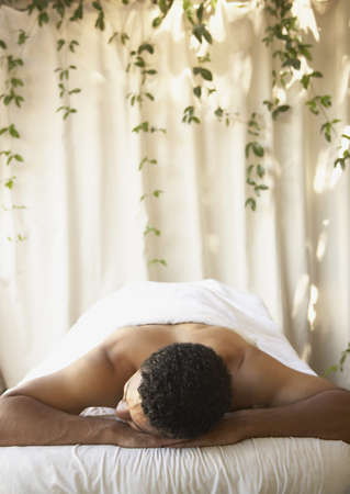 African man laying on massage table  LANG_EVOIMAGES