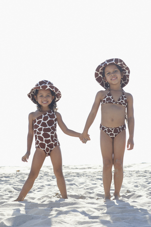 Young mixed race girls holding hands at beach LANG_EVOIMAGES