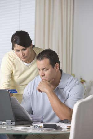 Hispanic couple paying bills online LANG_EVOIMAGES
