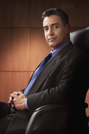 Hispanic businessman in office chair