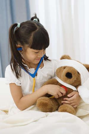 Pacific Islander girl examining teddy bear with stethoscope