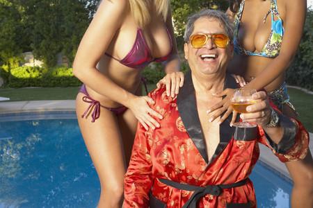 Playboy disfrutando de la piscina con novias jóvenes