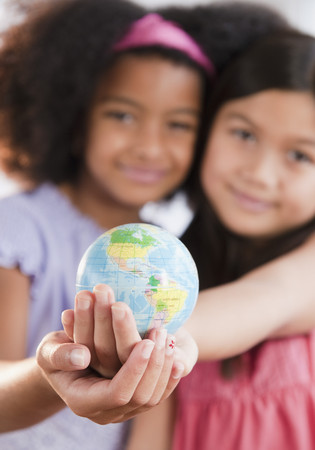Girls holding globe together