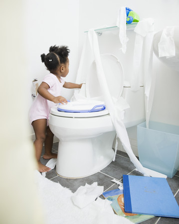 African American girl spreading toilet paper around bathroom