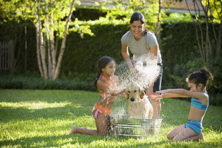 Hispanic mother and daughters washing dog LANG_EVOIMAGES