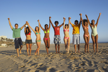 Multi-ethnic group of friends cheering on beach