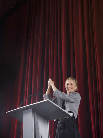 Businesswoman shaking own hand on stage
